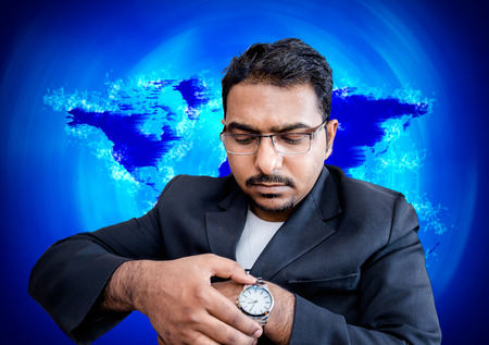 asian indian businessman with eye glasses fixing time on writ watch  on world map background photo