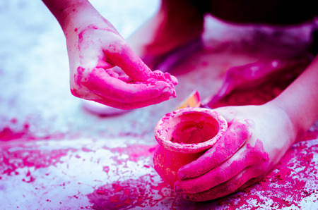 earthen: hands playing with colors    earthen pots background Stock Photo