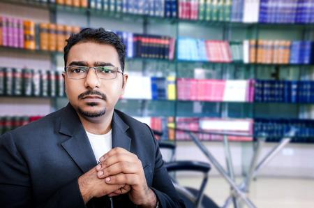 professional portrait: confident businessman portrait in office library folded hands