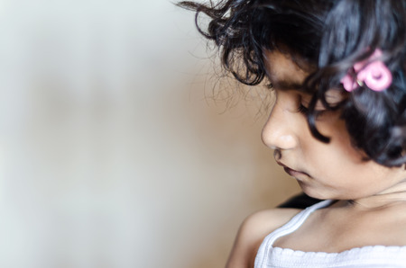 lonliness: child, alone, lonliness, solitude, sad, portrait, sideview, female, lifestyle, close up, candid, indian, asian, 5 year, looking left, indoor, horizontal, copyspace, copy ready, disturbed, calmness, Stock Photo