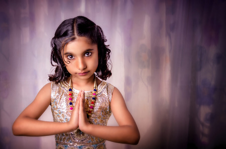 neckless: Portraint of small indian aisan girl child with folded hands saying Nameste a welcome gesture in fashionable modern designer dress and neckless against soft dreamy dress shot with Nikon D-5100 slight vignette added