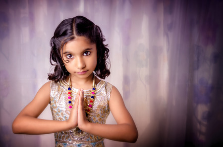folded hands: Portraint of small indian aisan girl child with folded hands saying Nameste a welcome gesture in fashionable modern designer dress and neckless against soft dreamy dress shot with Nikon D-5100 slight vignette added