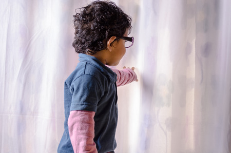 looking behind: Portrait of asian Indian boy child looking behind curtain wearing eye glass Stock Photo