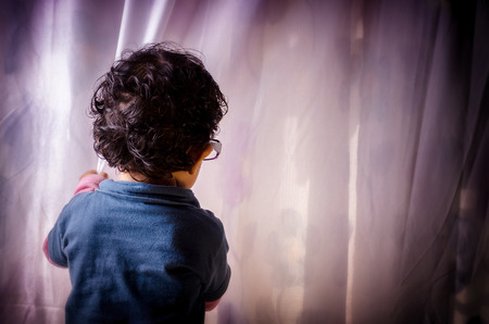 hide and seek: Portrait of asian Indian boy child looking behind curtain wearing eye glass Stock Photo