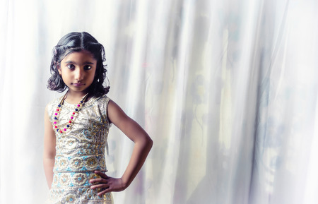 neckless: portrait of small 5-10 years old indian asian fashionable stylish glamourous girl child with big eyes and unique hairstyle and traditional lehnga chunni dress one hand on waist posing and  looking straight into the camera front view against textured curta Stock Photo