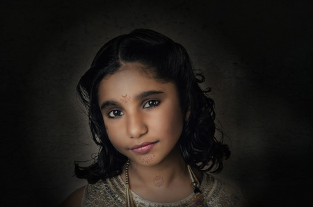 fashion model indian asian girl child closeup portrait with slight makeup and hairstyle and tribal girl style tatoo on face and neck