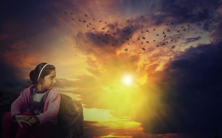 cc: small girl watching sunset sunrise while sitting on rocks or stones where sun shining through dramatic cloudy sky and birds are flying away in the sky. This scene was composed in the Adobe Photoshop cc 2014 using advance photomanipulation technique to giv