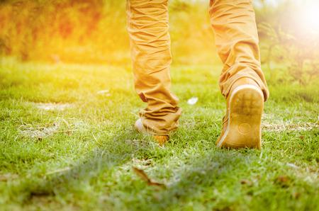 un caminar hacia un futuro más brillante, un hermoso tiro de pies caminando hacia la luz del sol o de seguir adelante towads amanecer o el atardecer en la hierba o parque o campo en ejecución o por la mañana a pie o hacer ejercicio, tono añadió