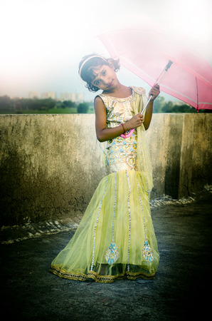 Indian girl child standing on roof holding umbrella in hands in fashionable indian traditional gown in daylight shielding her face from harmful sunrays sunlight shot with Nikon D-5100 with 50mm prime lens and post processed in Photoshop cc 2014