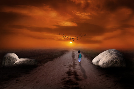 brighter: a little child walking alone towards the sunset or sunrise on a path to this magical and brighter future to search for his destiney big rocks are lying on both sides of the path depicting concept of forseeing future. composed in Adobe Photoshop cc 2014 us