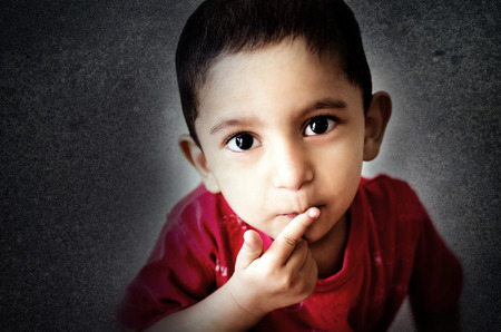 cc: indian asian boy little child putting finger on mouth with small hairs looking straight into camera headshot shot with nikon d-5100 with 35mm 1.8 g prime lens post processed in adobe photoshop lightroom and photoshop cc