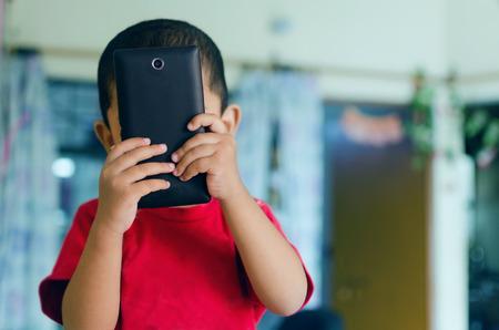 indiano ritratto asiatico bambino giocare con il cellulare nel salotto indossando rosso maglietta di colore o tee shot con nikon d-5100 con il 35mm 1.8g obiettivo primario elaborati in Lightroom e Photoshop