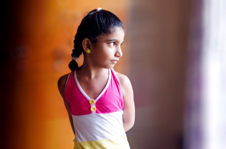 looking out: Portrait of indian asian girl child looking out towards light in casual dress clothes