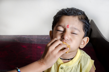 flavour: little indian asian boy child eating sweets with closed eyes enjoying the delicious flavour Stock Photo