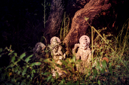 the idol or statues of abandoned lords Laxmi & Ganesh in the bushes under tree in forest or jungle or woods
