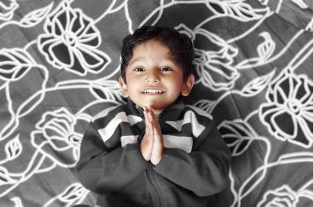 folded hands: indian asian boy child greeting with folded hands saying namaste