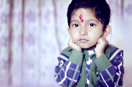 formal dressing: little asian indian child posing for camera looking into camera wearing shirt Stock Photo