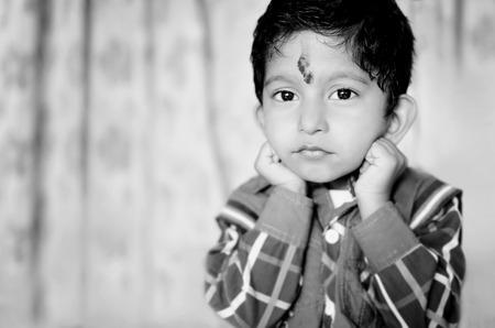 jardin de infantes: poco asi�tico ni�o indio posando para la c�mara que mira en la camisa c�mara que llevaba