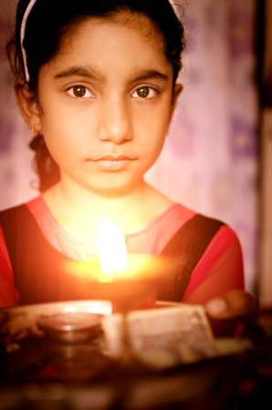 diyas: Girl child praying holding prayer plate with lighted lamp in hands
