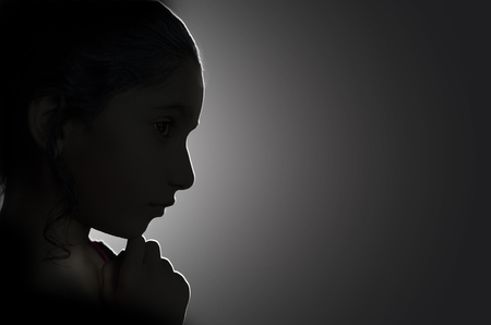close up view: Low key girl child hand on chin portrait side view backlit