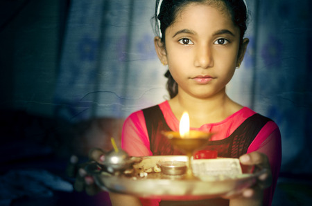diyas: Indian asian girl child fire art portrait holding prayer plate welcoming