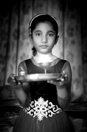 diyas: Indian asian girl child fire art portrait holding prayer plate welcoming