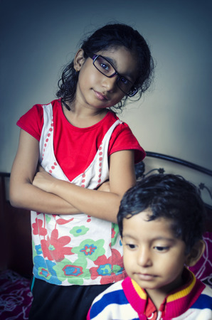 geeky: indian asian geeky girl child standing with folded hands with his brother indoor