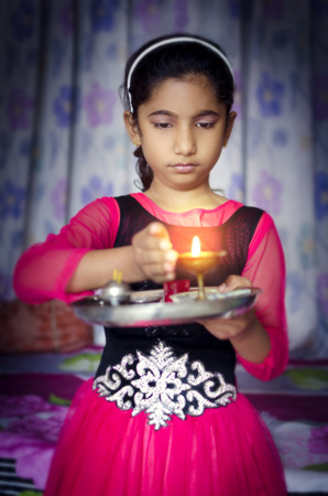 girl portrait: girl child portrait holding prayer plate protecting flame looking down Stock Photo