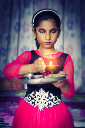 diyas: girl child portrait holding prayer plate protecting flame looking down Stock Photo
