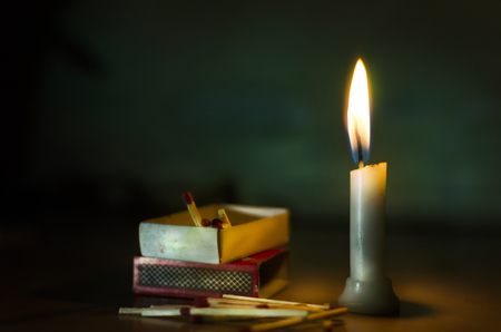 match box: stand in dark candle lit with match box and sticks lying on floor abstract concept Stock Photo