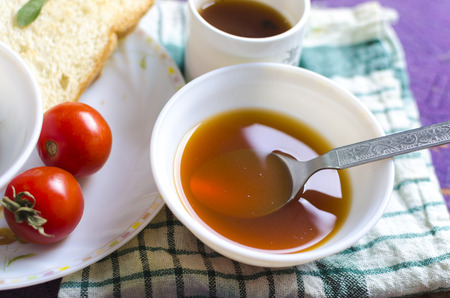bread slice: Delicious vegetables soup tomatoes soup in big bowl and raw tomatoes with bread slice and tea in background Stock Photo