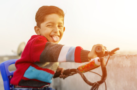 Indian asian Little cute boy child on bicycle or bike funny expression tongue out at morning sunset sunrise