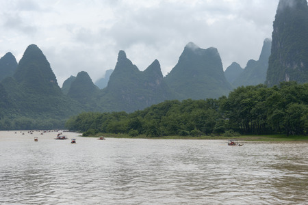 transcendental: small boats on Li river in China against transcendental mountains and tropical vegetation
