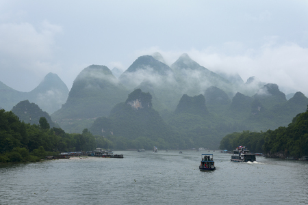 transcendental: small boats and the cruise ships on Li river in China against transcendental mountains and tropical vegetation Stock Photo