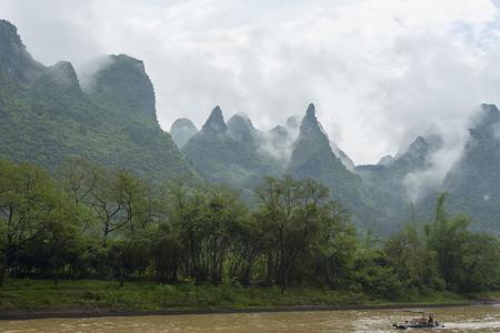 transcendental: small boat on Li river in China against transcendental mountains and tropical vegetation