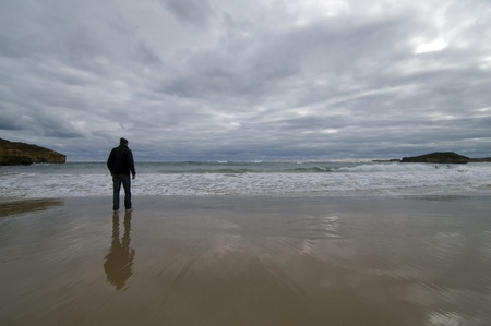 Lonely Man facing the ocean photo