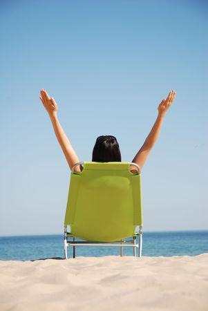 Mujer disfrutando del sol en la cubierta de silla Foto de archivo