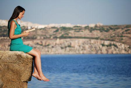 Joven leyendo el libro por el mar