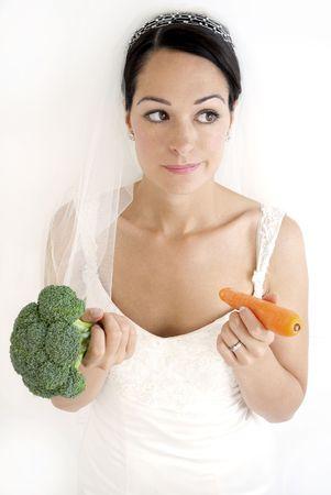 bridal dress: Opzioni sano sposa holding broccoli e una carota in parte del suo contenuto calorico controllato dieta  Archivio Fotografico