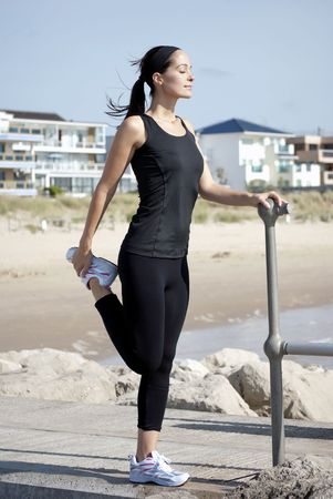 woman holding on to pole to do stretching exercise on the beach