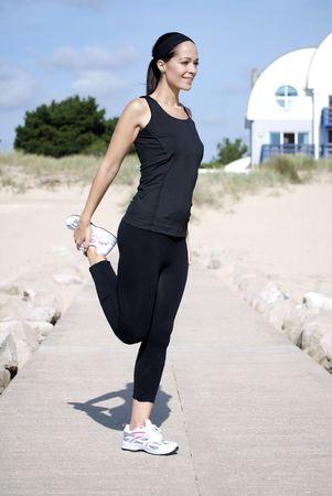 Mujer haciendo ejercicios de strecthing en la playa  Foto de archivo