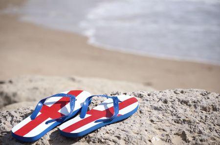 Escena de playa con flip flops mostrando la Cruz de San Jorge  Foto de archivo
