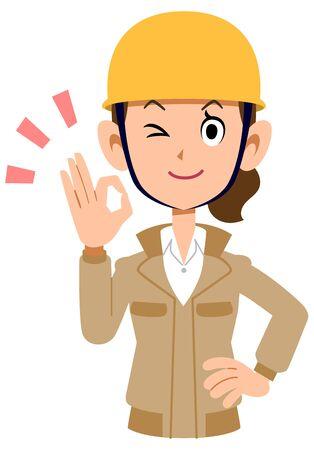 A woman wearing a helmet wearing a beige work clothes giving an OK sign