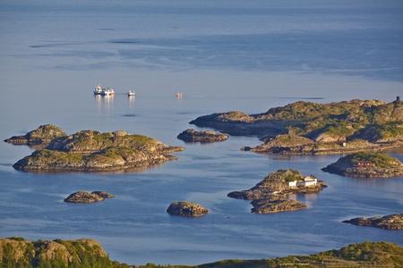 islets: Houses of fishermen on tiny islets on Lofoten Islands near Henningsvaer, Norway Stock Photo
