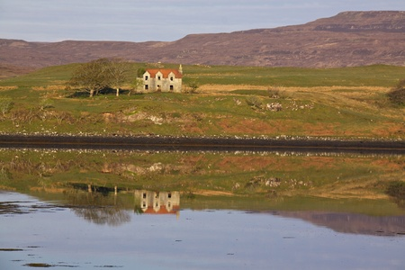 Old house on Isle of Skye, Scotland, reflecting in the water of loch photo