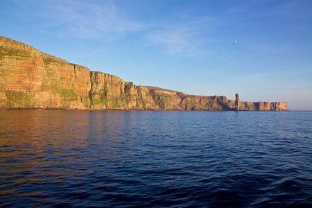 Cliffs with layers of red sandstone on the western coast of Orkney Islands photo