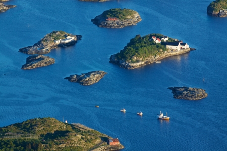 Bird eye view of fishing boats sailing between scenic islets near Henningsvaer on Lofoten islands in Norway Stock Photo