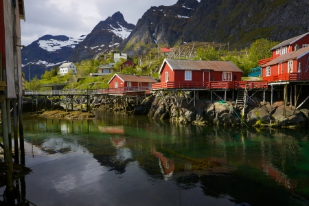 Typical red rorbu fishing huts on Lofoten islands in Norway reflecting in fjord photo