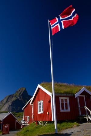 Norwegian flag with typical norwegian red wooden house with sod roof on Lofoten islands photo
