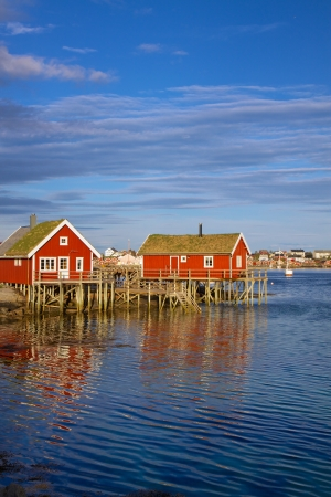 Red fishing rorbu huts by the fjord in town of Reine on Lofoten islands photo
